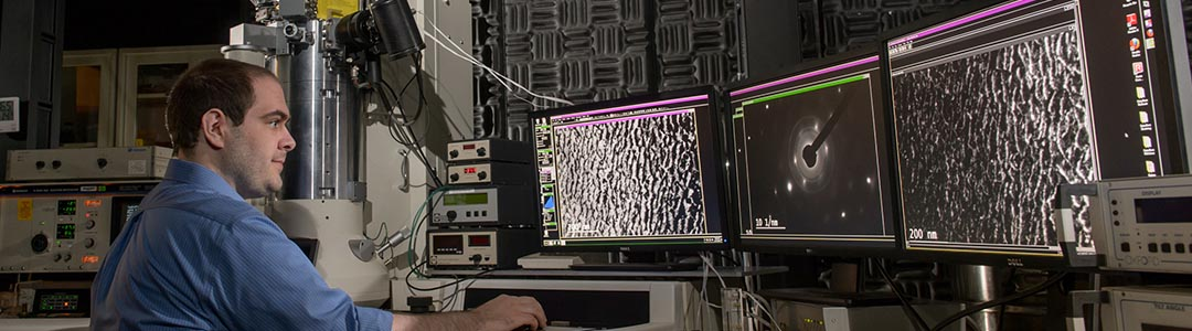 a researcher works at a 3-monitor array in a lab